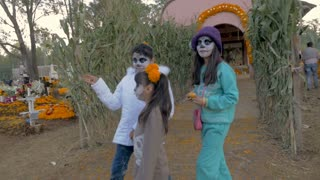 "TZURUMUTARO, MEXICO - NOVEMBER 1, 2016 - Three young Mexican girls wearing the traditional sugar skull makeup ""La Catrina"" in a cemetery outside of Patzcuaro during Day of the Dead"
