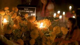 TZURUMUTARO, MEXICO - NOVEMBER 1, 2016 - Two young Mexican girls decorating a grave with flowers during day of the dead
