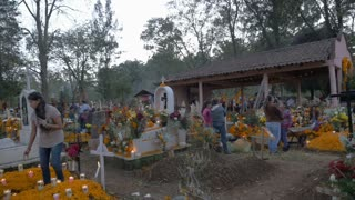 TZURUMUTARO, MEXICO - NOVEMBER 1, 2016 - Wide establishing shot of many Mexican families preparing graves in a cemetery for Day of the Dead