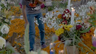 TZURUMUTARO, MEXICO - NOVEMBER 1, 2016 - Young Mexican teenage boy lighting candles at a grave alter for day of the dead