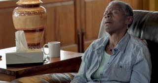 Unhappy sick senior black woman in her 60s sneezing and wiping her nose with symptoms of a cold, allergies, or the flu