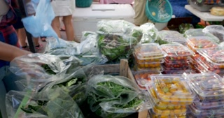 Vender restocking fresh organic vegetables including spinach and arugula in plastic bags at a farmers' market while people are shopping