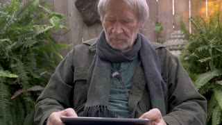 Vibrant healthy mature man in his 70s reading a digital tablet on his lap outside in his garden