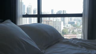 View from a bedroom overlooking a modern urban city with skyscrapers and tall buildings