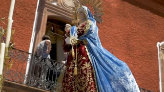 Virgin Mary statue with a blue robe blowing in the wind in slow motion during an Easter parade during Semana Santa holy week celebration