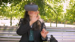 Virtual reality working millennial businesswoman in her 30s wearing VR headset technology sitting outside on park bench in slow motion hand held