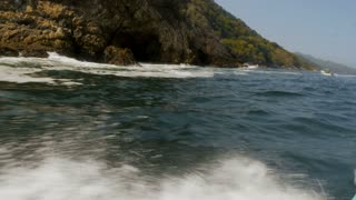 Water crashing along the side of a boat traveling near a mountainous shore line along the ocean in slow motion