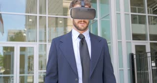Well dressed handsome millennial man in a business suit leaves his virtual reality world removing his VR headset and is disappointed in the real world in 4k
