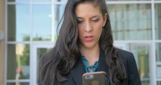 Well dressed woman in her 30s on her smart phone app technology looks up and smiles at the camera outside a modern office building in 4k