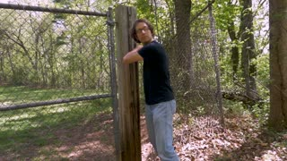 Wide of a man breaking into a chained off area and creeping into the woods in slow motion