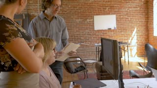 Woman boss reviewing data graphs and charts on her computer monitor with her employees in a modern creative business startup office in slow motion stabilized shot