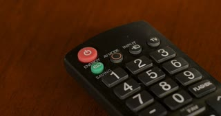 Woman pushing the energy saving button on a television remote control - close up