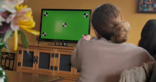 Woman using a TV remote control on a green screen television sitting next to a teenager
