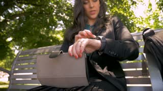 Woman wearing business fashion with digital tablet and smart watch syncing the two devices while sitting on park bench slow motion low angle