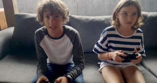 Young 11 -12 year old boy and girl play video games with a handheld controller while sitting on sofa and talking to each other - stabilized shot