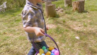 Young 4 - 5 year old cute boy concentrating on finding easter eggs while walking in a yard in slow motion