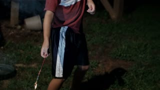 Young 8 year old boy holding a fireworks sparkler away from his body as it burns in his hand at night in slow motion