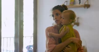 Young attractive stay at home mother holding a toddler baby talking to someone off camera