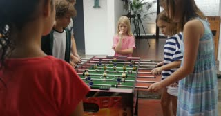 Young children playing foosball together boys against girls at a party, social event, or summer camp