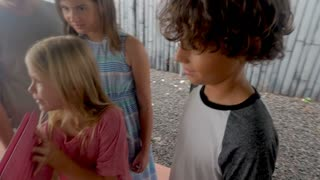 Young girl scratching her leg while looking at a digital tablet with her friends in slow motion outside