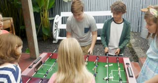 Young girls against young boys playing foosball and the girls score to win the game
