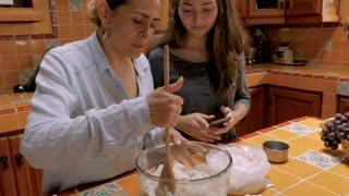 Young mixed race teenager holding smart phone cooking and laughing with a Mexican mid adult woman - slow motion