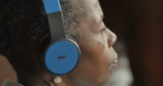 Youthful attractive healthy black senior woman in her 50s or 60s listening to music with headphones - profile