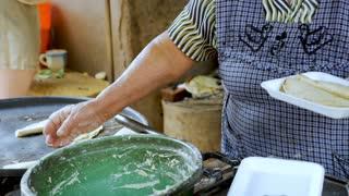 ZIRAHUEN, MEXICO - CIRCA MAY 2018 - Elderly indigenous woman making street food in her outdoor kitchen in slow motion