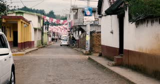 ZIRAHUEN, MEXICO - CIRCA MAY 2018 - Rural cobblestone street in the mountains of Michoacan with colorful flags (papel picado) hanging between houses during the day