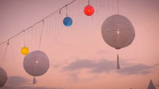 White and colored lanterns blow gently in the breeze against the colored sky at sunrise or sunset with christmas lights gently swaying in the wind.
