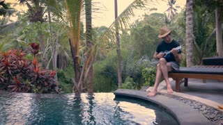 Wide shot of a young middle aged man wearing a straw hat and playing a ukulele by an infinity pool in the jungle at a luxury resort, hotel, or villa in Ubud, Bali.