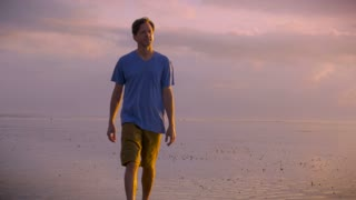 Young adult man in a blue t shirt and short pants smiles and walks alone on the beach with the ocean in the background and beautiful colors in the clouds at sunrise or sunset. He looks inspired and grateful for the beauty around him.