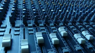 Slide along an audio mixing console. Audio mixer faders and knobs. Music production and sound engineering background. 4K footage.