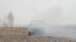 Car in the smoke in an empty field. Front view