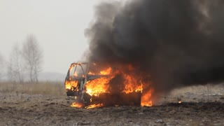 Car on fire in an empty field. Front view. Slow-mo