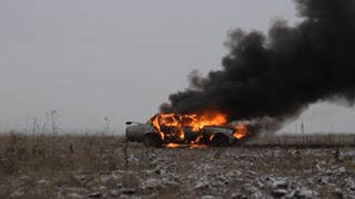 Car on fire in an empty field. Side view