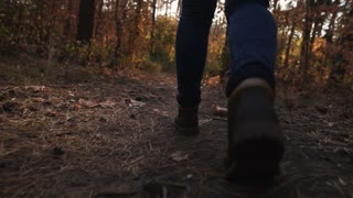 Feet. Boots. Girl walking along in the autumn forest. Steadicam shot