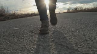 Feet. Boots. Girl walking along the road. Steadicam shot
