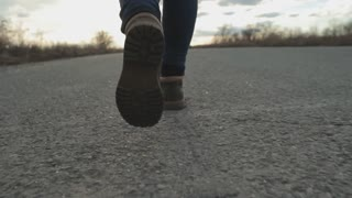 Feet. Boots. Girl walking along the road. Steadicam shot
