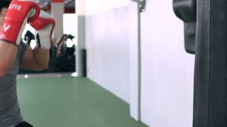 Fighter Trains With Punching Bag In The Gym. Slow-Mo