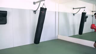 Fighter Trains With Punching Bag In The Gym