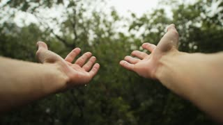 Hands get wet in the rain on a blurred background of trees