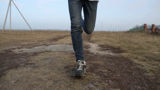 Man running fast on a dirt road. Feet. Shoes. Steadicam shot
