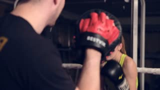 Pretty young woman exercising with trainer at boxing and self-defense lesson in basement
