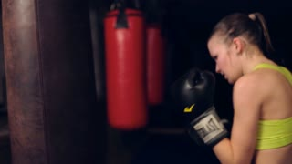 Pretty young woman working out, boxing, exercising for self-defense in basement