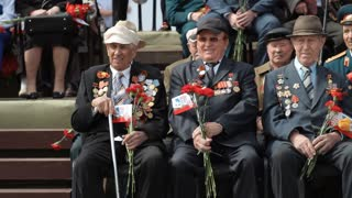 Russia, TolyattI, May 9, 2015: Children give flowers to veterans of  World War II, military parade. Victory Day