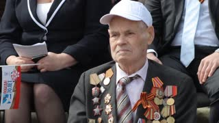 Russia, TolyattI, May 9, 2015: Veteran of World War II in a wheelchair, military medals, military parade. Victory Day