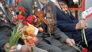 Russia, TolyattI, May 9, 2015: Veterans of World War II with flowers, military medals, military parade. Victory Day
