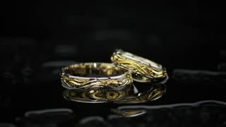Gold Rings On Black Wet Surface On Black Background