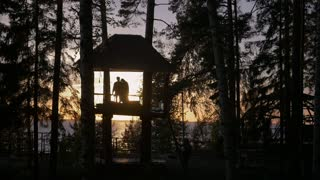 Young Couple In Tree House At Sunset Near The Sea